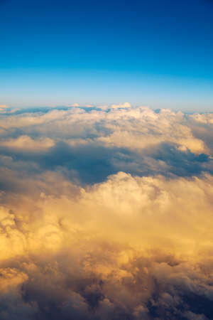 Sunny sky abstract background, beautiful cloudscape, on the heaven, view over white fluffy clouds, freedom concept. Aerial view of sky and white clouds. View from airplane.