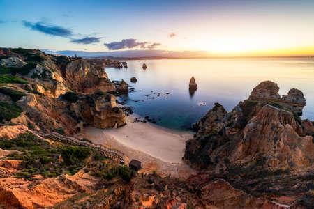 Sunrise at Camilo beach in Lagos, Algarve, Portugal. Wooden footbridge to the beach Praia do Camilo, Portugal. Picturesque view of Praia do Camilo beach in Lagos, Algarve region, Portugal. 免版税图像