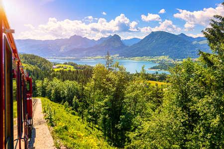 Schafbergbahn mountain train, Schafberg mountain, Salzkammergut region, Salzburg Land state, Austria. Journey to the top of Alps through lush fields and green forests.View of lake Wolfgangsee.