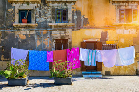 Siracusa (Syracuse) in a sunny summer day. Sicily, Italy. The clothes being dried in the narrow street of the famous historic town Syracuse, Sicily.