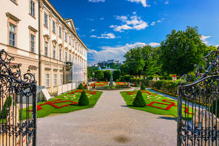 Beautiful view of famous Mirabell Gardens with the old historic Fortress Hohensalzburg in the background in Salzburg, Austria. Famous Mirabell Gardens with historic Fortress in Salzburg, Austria. Editoriali