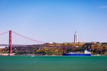 The 25 April bridge (Ponte 25 de Abril) is a steel suspension bridge located in Lisbon, Portugal, crossing the Targus river. Cristo Rei or Christ the King in the background. Lisbon. Portugal. Editoriali