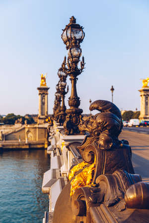 Pont Alexandre III bridge over river Seine in the sunny summer morning. Bridge decorated with ornate Art Nouveau lamps and sculptures. The Alexander III Bridge across Seine river in Paris, France. Editoriali