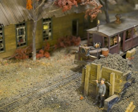 Little Model Rail Road scene of a worker taking a break while the old train pulls up. photo