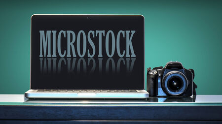 window display: Laptop and reflex camera over a desk with aquamarine background, the computer shows a fictitious micro stock site
