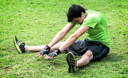 touching toes: Young man at the park warming and stretching on the grass Stock Photo
