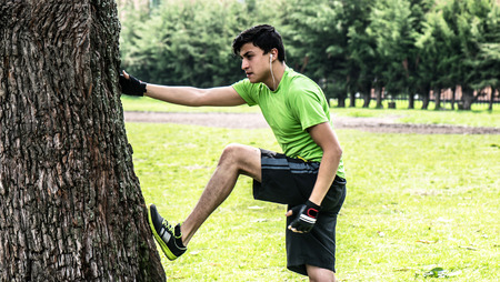 touching toes: Young man at the park warming and stretching with a tree