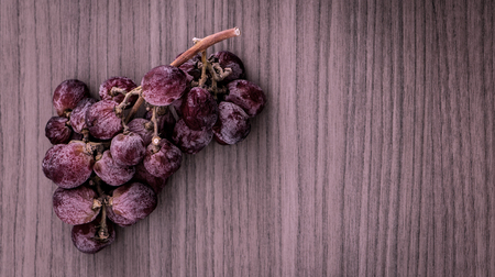 grape juice: A bunch of overripe red grapes on wood