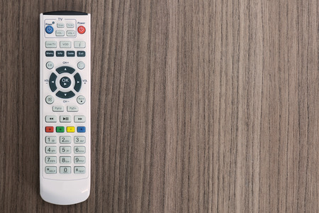 electronics equipment: A remote control over a wood background Stock Photo