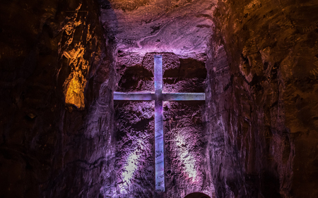 Beautiful christian cross carved in the rock and lighted by colored lights