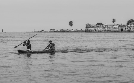 limosna: CARTAGENA, COLOMBIA - JUNE 6, 2015: Young fishermen on the outskirts of Cartagena who also earn money jumping from their canoes for the coins launched by tourists to the sea