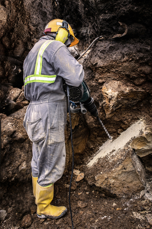 Workerman with helmet and protective suit using drill-machine in an underground environment Reklamní fotografie