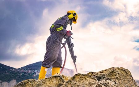 Werknemer met helm en beschermende pak met behulp van een boormachine op de top van een grote rots