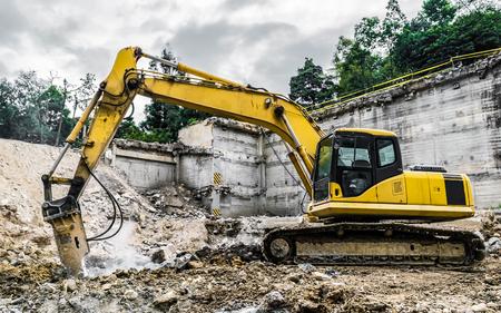 Demolition machine crushing debris of old estructure