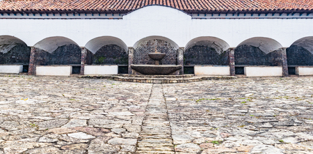 Central square of Spanish colonial architecture with water fountain and stone floor