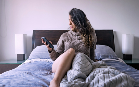 Latin woman watching the cell phone in her bedroom wearing a comfortable sweater as pajama