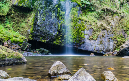 Long exposure of crystal clear water flowing down a green mountain full of moss and vegetation, Choachi, Cundinamarca, Colombia. Reklamní fotografie