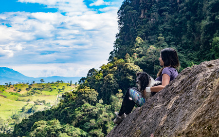 Latin woman and her dog contemplating the horizon on a rock in the top of a montain of a natutal park of Colombia.