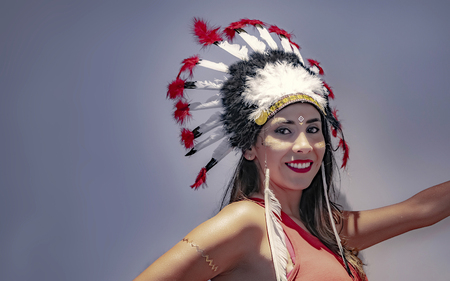 Portrait of a latin model with a feathered headdress with lights and shadows accentuated on her face