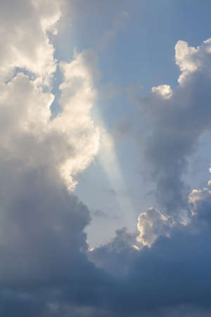 Clouds on blue sky pierced by ray of sunlight, vertical