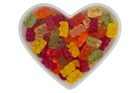 Heart-shaped bowl filled with gummy bears, isolated on white background 版權商用圖片