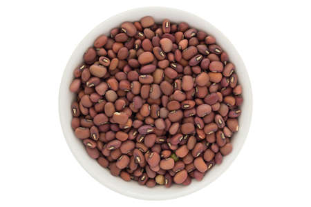 Dried red azuki beans in white bowl, isolated on white background