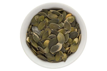 Pumpkin seeds in white bowl, isolated on white background 版權商用圖片