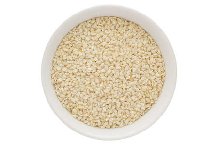 Sesame seeds in white bowl, isolated on white background