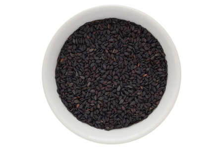 Black sesame seeds in white bowl, isolated on white background