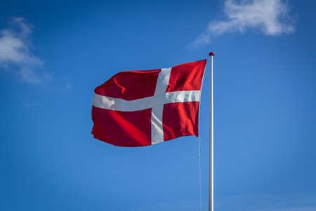 Bandeira dinamarquesa sob a luz do sol contra o céu azul com nuvens, horizontal Foto de archivo - 81720698