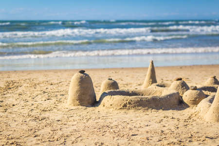 Sand castle on beach with waves in background, shallow depth of field, horizontal 版權商用圖片