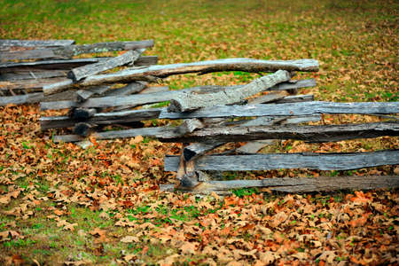 split rail: Split rail fence in the fall with leaves covering the grass. Stock Photo