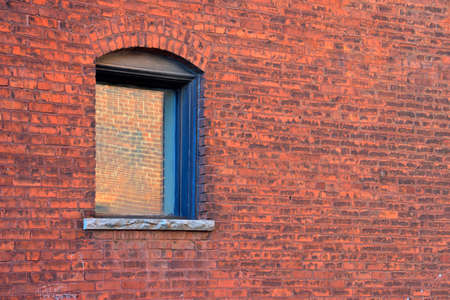 window opening: An arched window opening in a vintage brick wall.