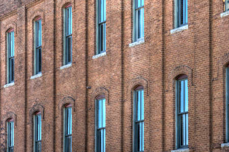 brick building: A large number of wooden sash windows in an old industrial brick building