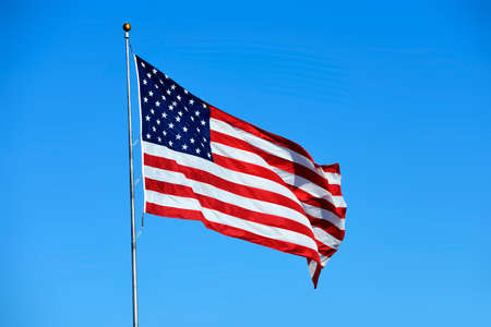 flapping: US American flag flapping in the wind with clear blue sky background Stock Photo