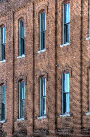 sash: A large number of wooden sash windows in an old industrial brick building