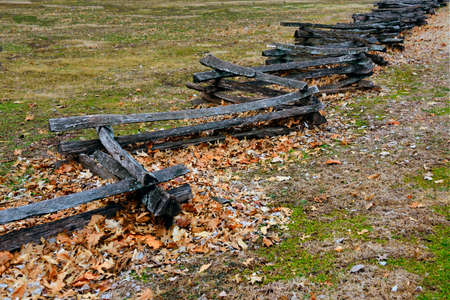 split rail: Split rail fence during the fall-winter season with leaves covering the grass. Stock Photo