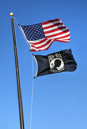 bereaved: The American Flag with the POW MIA Flag flying against a blue sky.  The POW MIA flag is a symbol of US military personnel taken as prisoners of war or listed as missing in action. Stock Photo