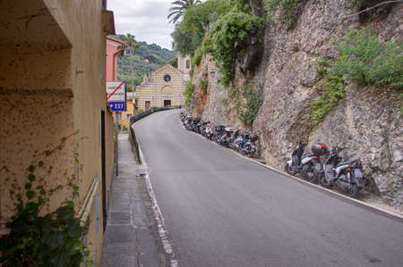 Portofino, Italy - 05182016 - A row of motor scooters parked along a bluff on the road to Portofino, Italy.