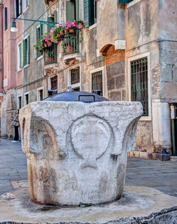 Old water well in a town square in Venice, Italy