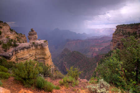 Grand Canyon framed by outcrops with rain storm approaching. Stock Photo