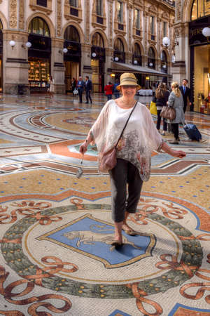 MILAN, ITALY - MAY 23, 2017: A tourist spins her heels on the testicles of a bull mosaic (coat of arms of Turin) in Galleria Vittorio Emanuele.  Tradition says three turns may bring good luck. Redactioneel