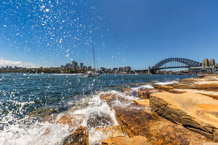 View of Harbor Bridge with a boat sailing in the distance and water splashing in the foreground in Sydney, Australia