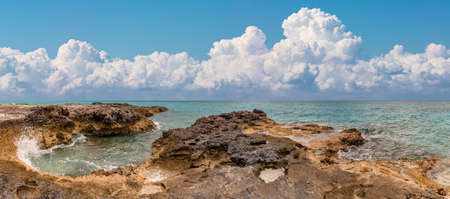 Beautiful panoramic view of a rocky beach in tropics. Turquoise water splashing in the foreground. Scenic blue sky with amazing white clouds as a back