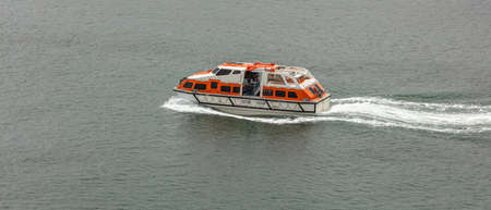 Orange-and-white life boat moving fast in the water. Life saving equipment concept. Stok Fotoğraf