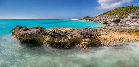Beautiful panoramic view of a cliff in tropics. Turquoise water. Blue sky as a background. Long exposure.