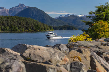 Fishing speedboat sailing fast in harbor. Beautiful yellow trees and rocks in soft focus in the foreground. Mountains, and forest in the background. Stockfoto - 150297095