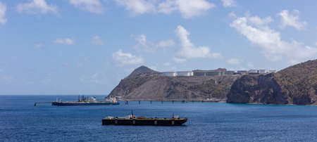 St. Eustatius island. Panorama of huge fuel tanks up on the hills and fueling barges in the front. Stockfoto - 150297711