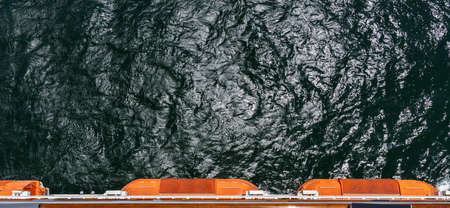 View from the top of a sailing cruise ship. Life boats sticking out. Cruising concept.