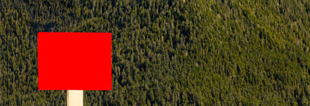 Blank red sign in the foreground and forest, mountains, blue sky with clouds in the background Stockfoto - 150297676